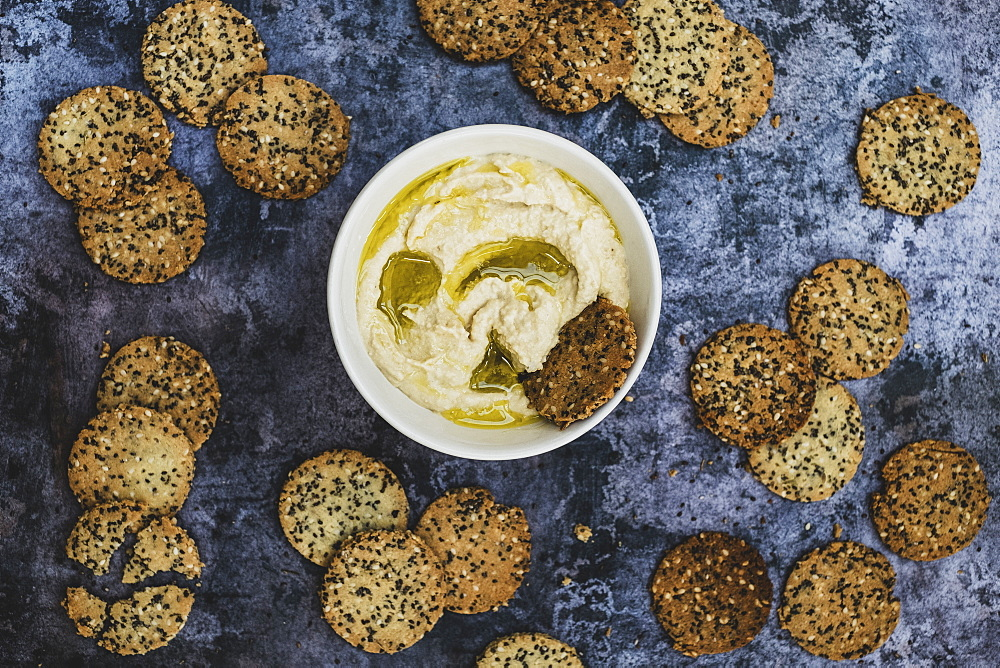 High angle close up of a bowl of hummus and freshly baked seeded crackers, England