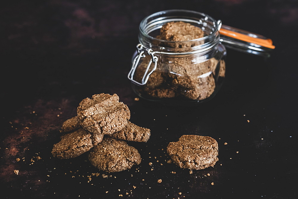 High angle close up of freshly baked chocolate cookies in a glass jar, England