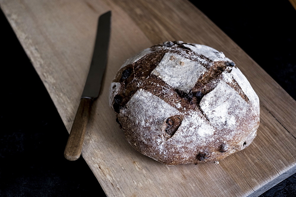 A loaf of freshly baked brown bread with a thick crust on a bread board, England - 1174-6589