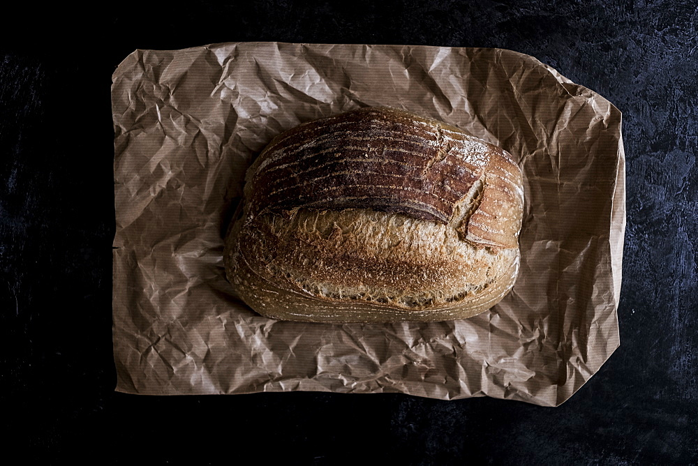 A fresh loaf of baked bread on a brown paper bag, England - 1174-6590