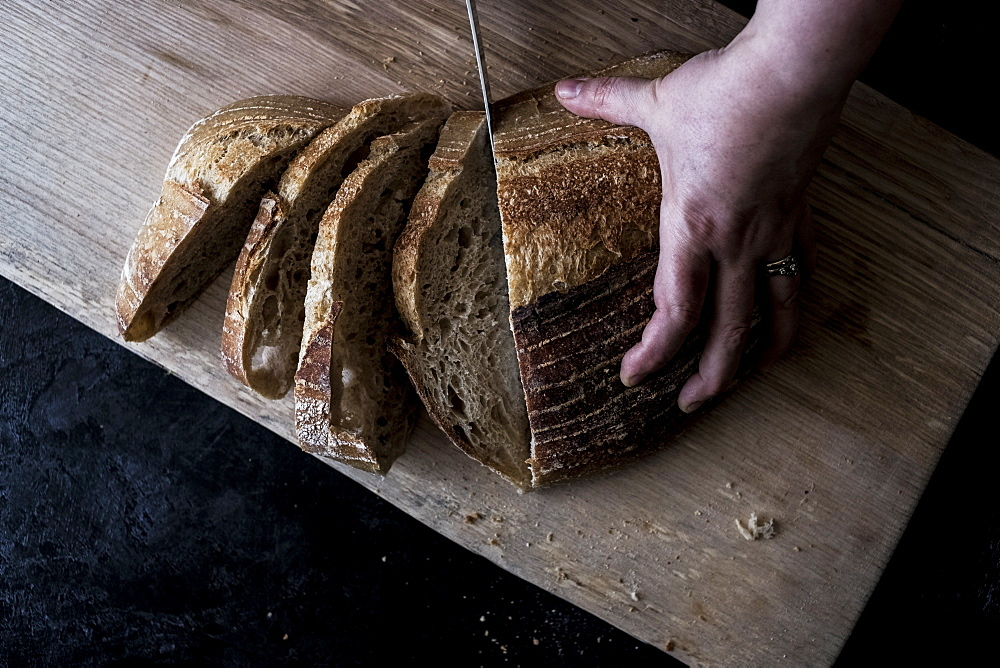 A hand holding a loaf of bread and using a breadknife to cut slices, England