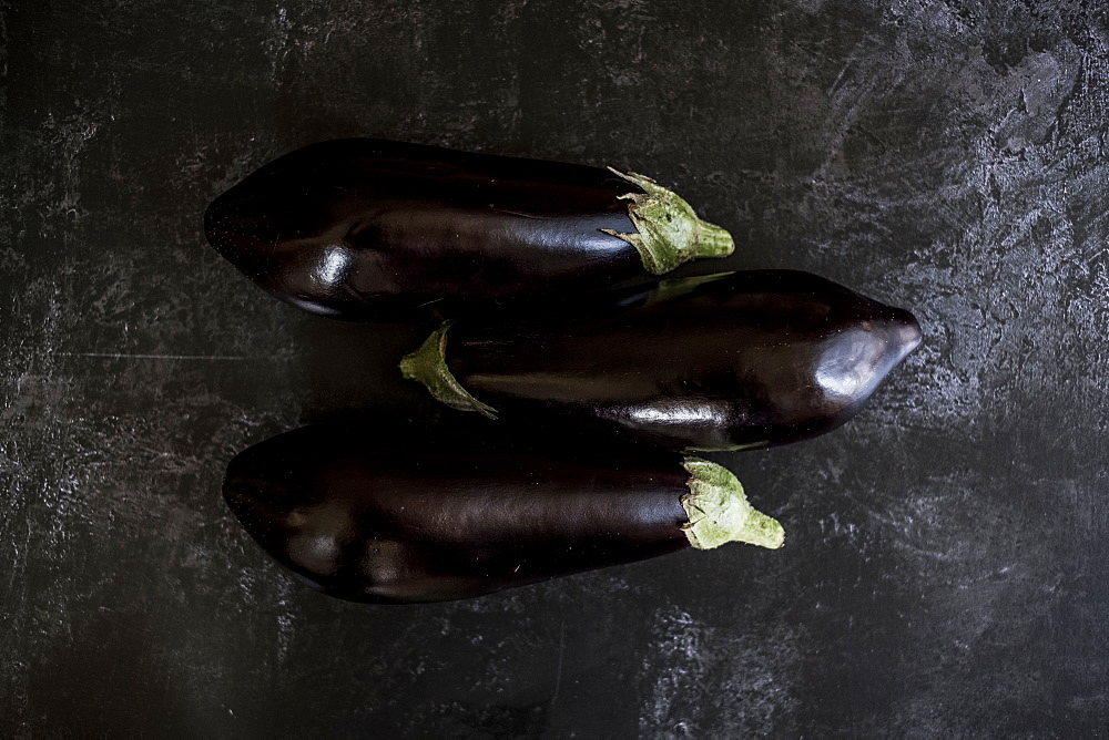 Three glossy purple aubergine egg plant vegetables on a grey slate background, England - 1174-6592