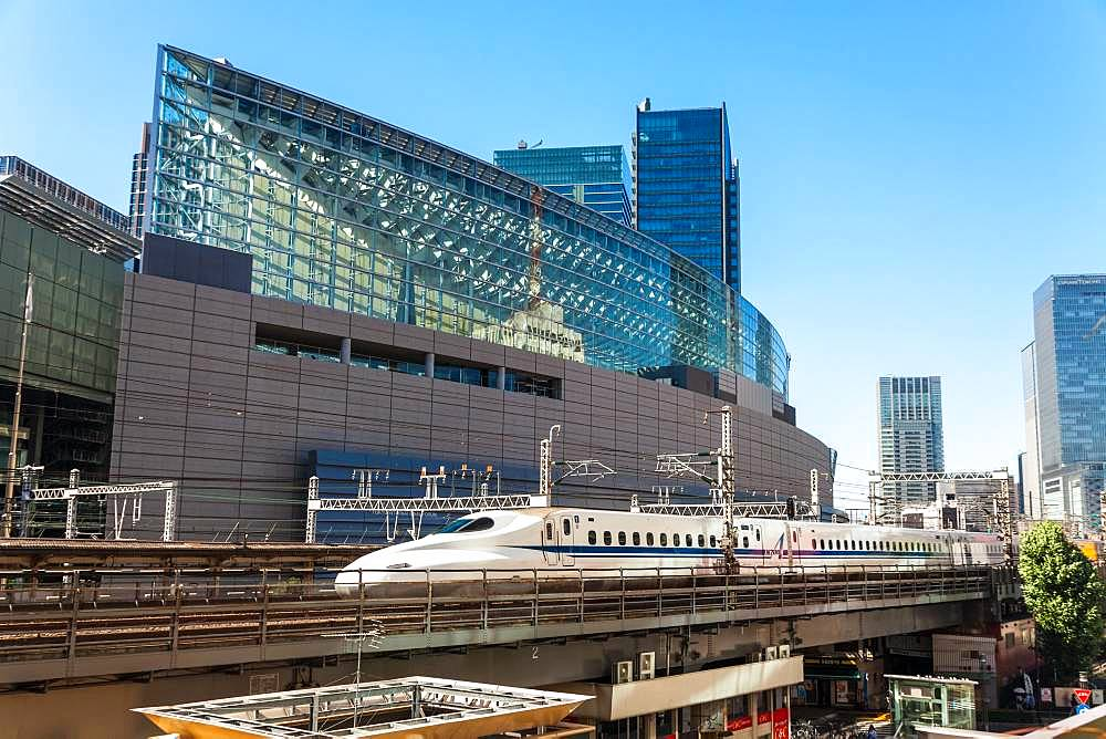 Shinkansen Bullet Train on an elevated section of track next to the Tokyo International Forum by Yurakucho Station, Tokyo, Japan