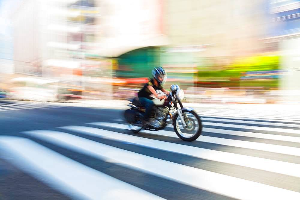 Motion blurred shot of a motorbike at speed on a pedestrian crossing in Tokyo, Japan