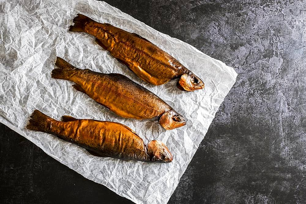 High angle close up of three freshly smoked whole trout on a white paper