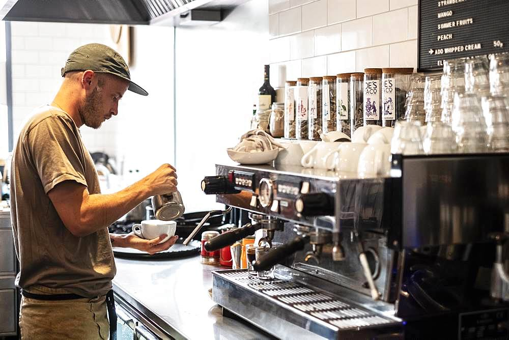 Bearded man wearing baseball cap standing at espresso machine a restaurant