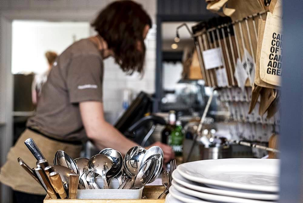 Close up of stack of plates and container with cutlery in a restaurant, woman working in background