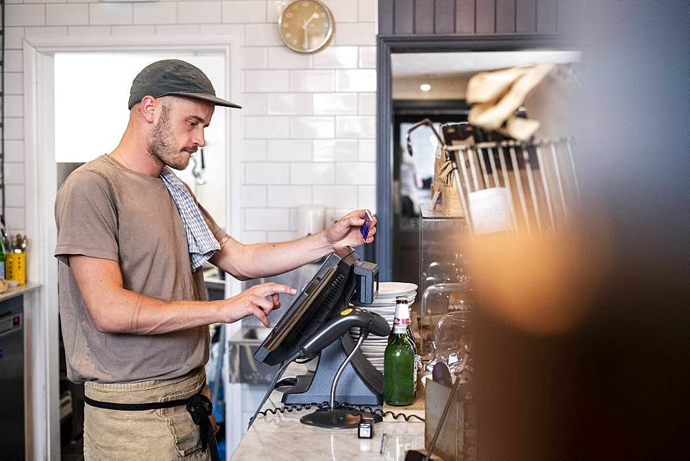 Bearded man wearing baseball cap standing at a till in a restaurant