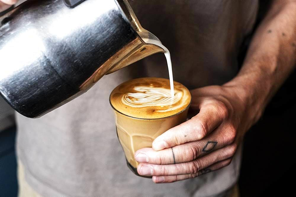Close up of person with tattooed finger pouring milk from metal jug into glass of cafe latte