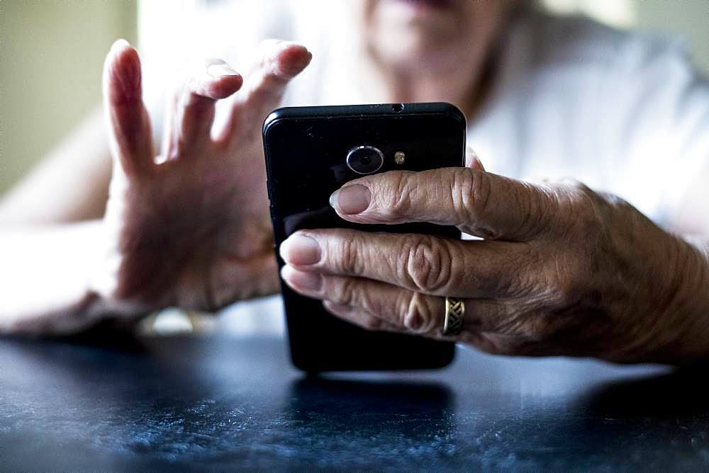 Close up of senior woman sitting at a table, using mobile phone