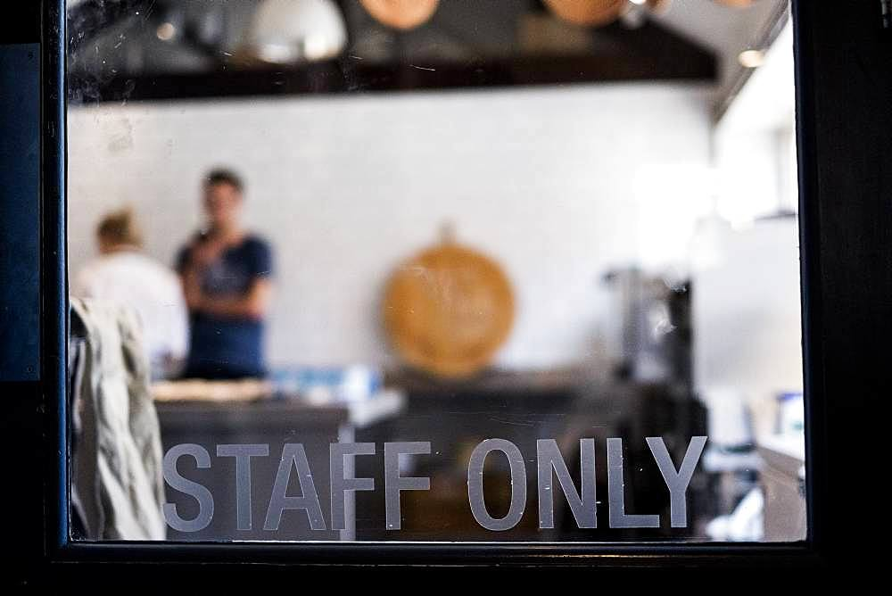 View through a door marked Staff Only to a commercial kitchen and two people working