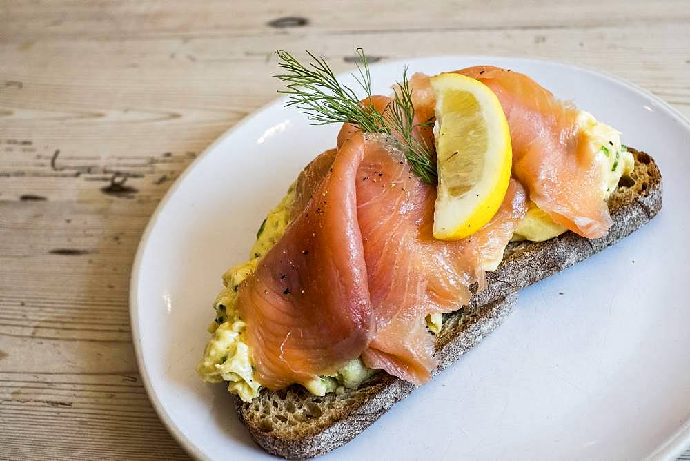 An open sandwich on rye bread with a topping of cured salmon or fish with garnish of a slice of lemon