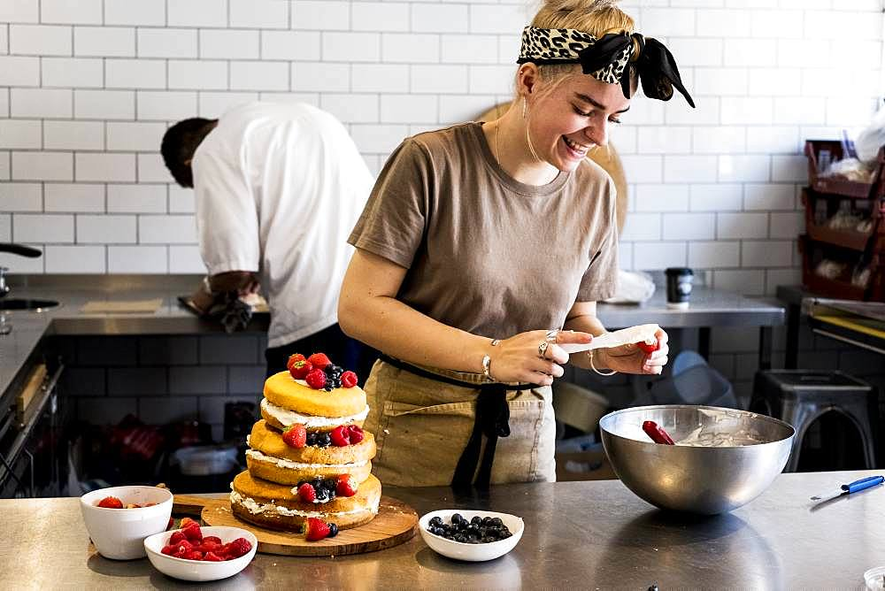 A cook working in a commercial kitchen assembling a layered sponge cake with fresh fruit
