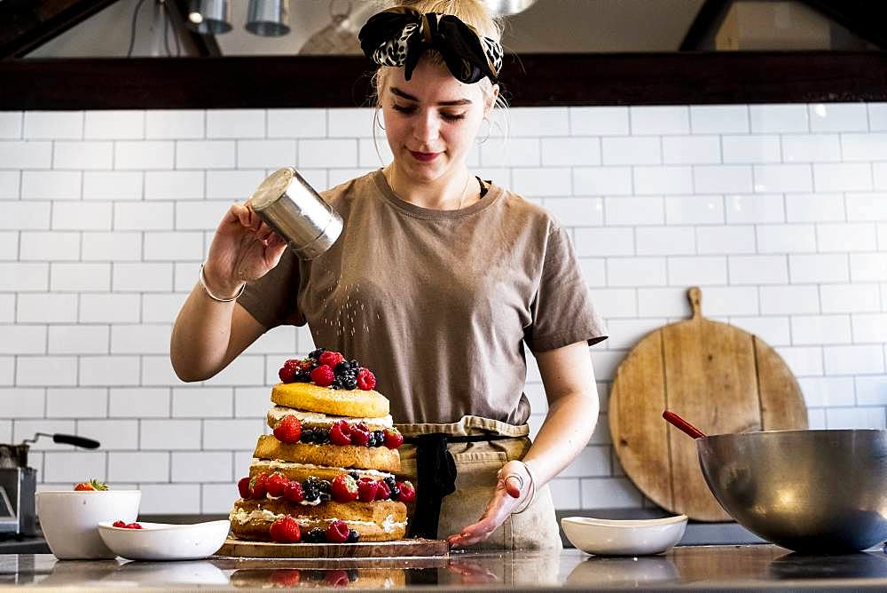 A cook working in a commercial kitchen sprinkling icing sugar over a layered cake with fresh fruit
