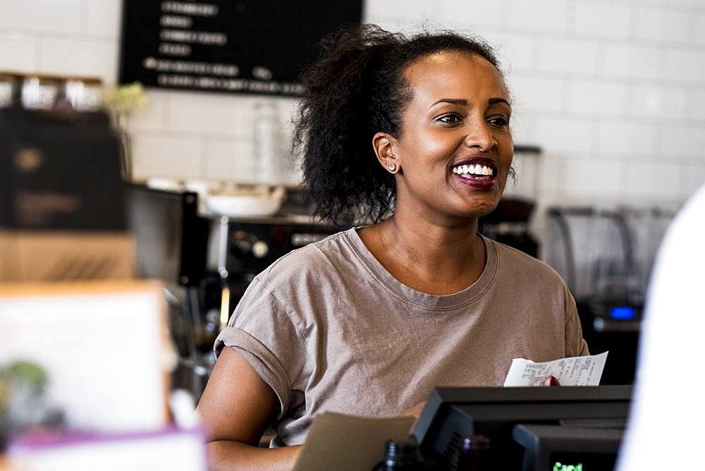 A woman barista smiling in welcome beside the counter in a coffee shop
