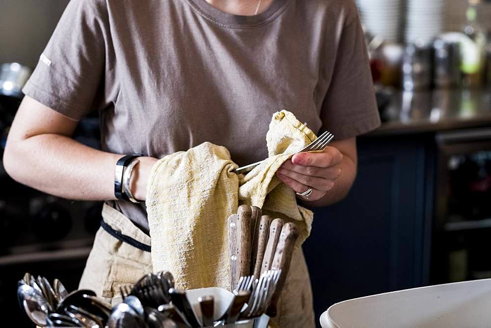 A staff member drying cutlery in a cafe