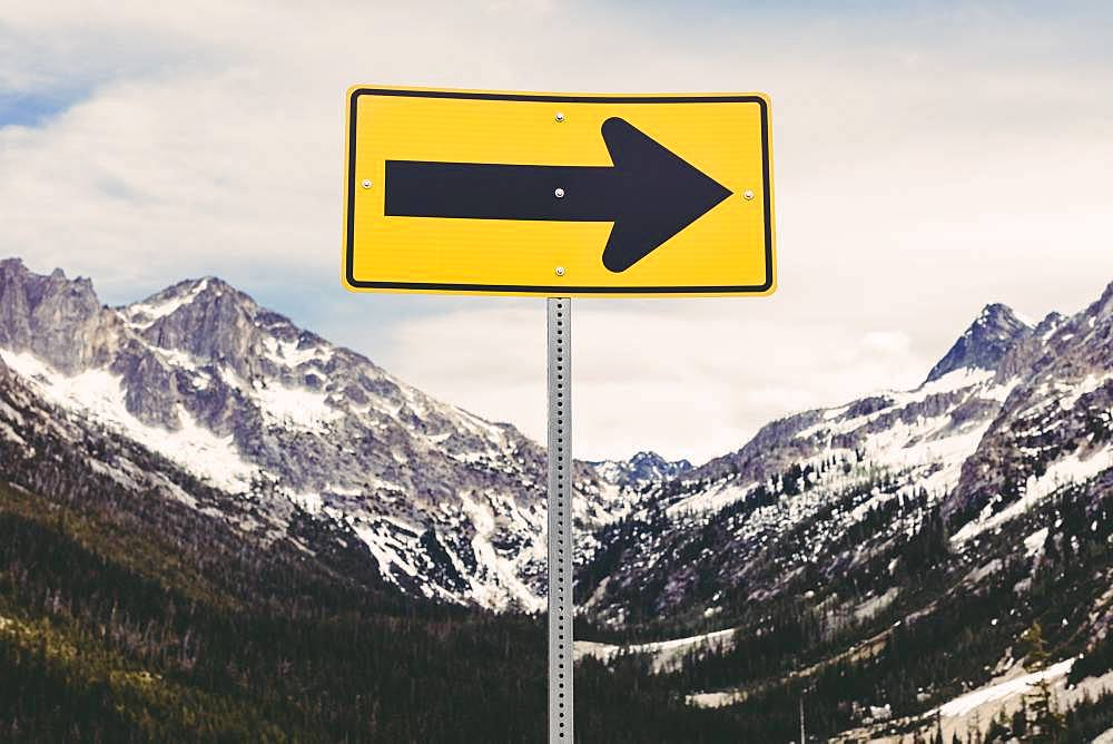 Directional arrow sign in a snow covered mountain range
