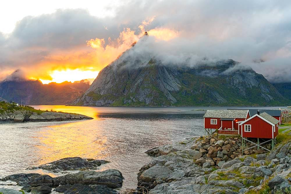 Low clouds swirling round and covering the mountains, a small traditional rorbu house on the shoreline Lofoten Islands, Norway