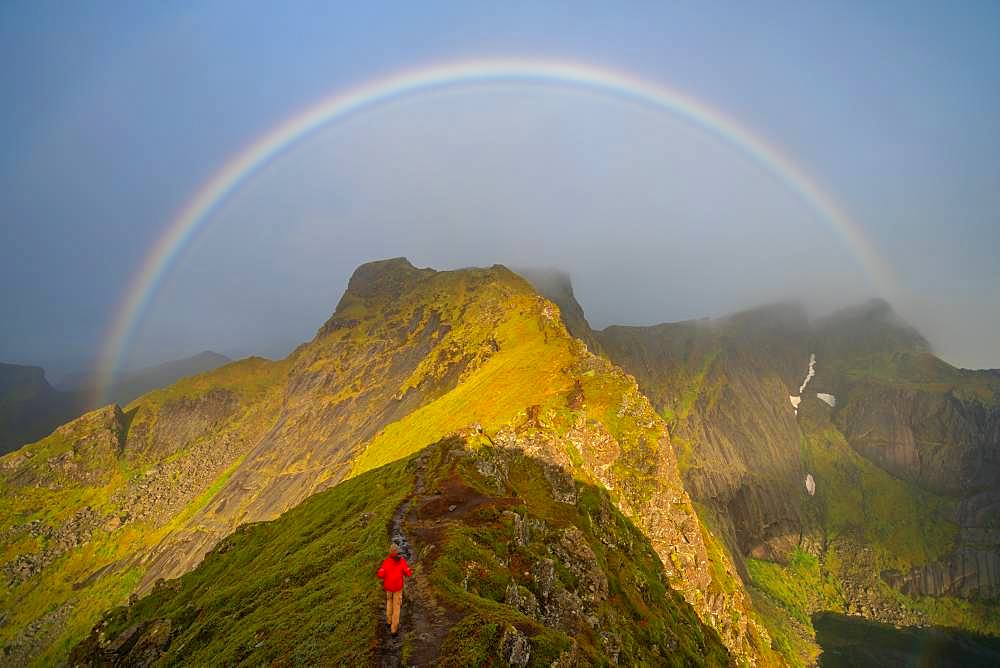 Man climbing towards a rainbow in the Lofoten Islands, Norway
