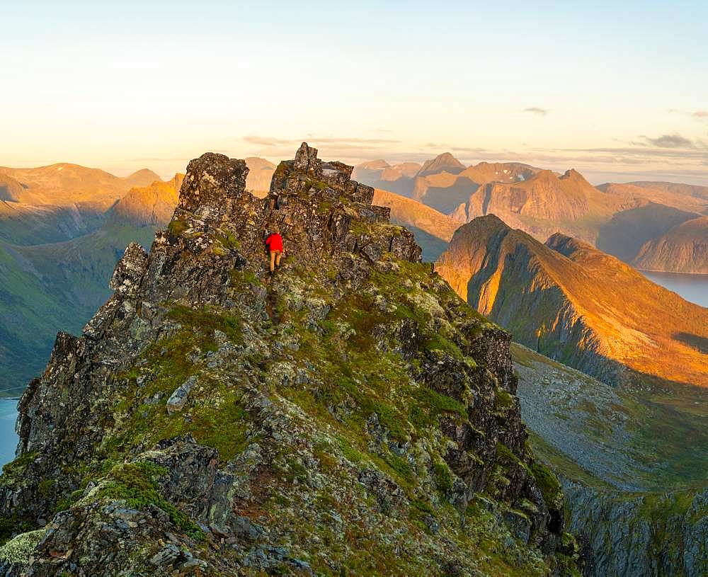 Man climbing up a steep peak in the jagged landscape of Senja Island, Troms, Senja Island, Lofoten Islands, Norway