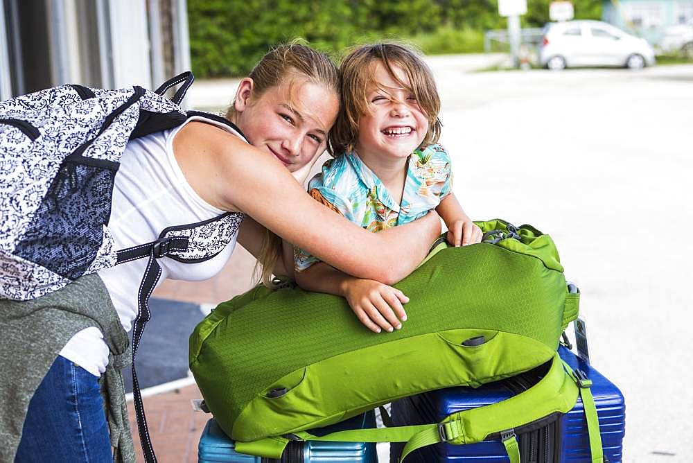 13 year old sister and her 5 year old brother leaning on travel luggage, Grand Cayman, Cayman Islands