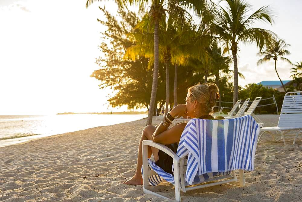 Adult woman sitting in beach chair on holiday, Grand Cayman, Cayman Islands