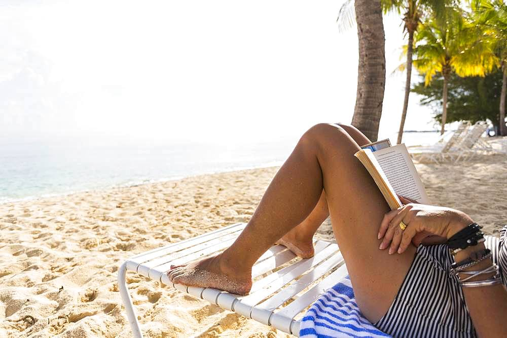 A woman lying on a sandy beach in the shade reading a book, Grand Cayman, Cayman Islands