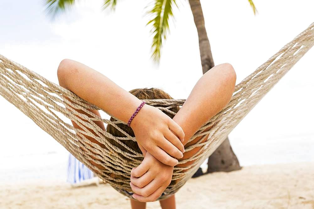 A teenage girl relaxing in a hammock, Grand Cayman, Cayman Islands