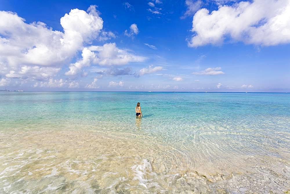 A teenage girl standing in the ocean, Grand Cayman, Cayman Islands