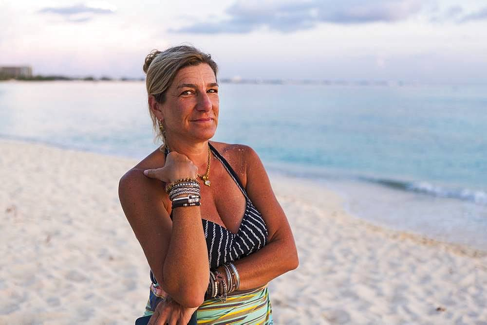 Adult woman looking at setting sun, Grand Cayman, Cayman Islands