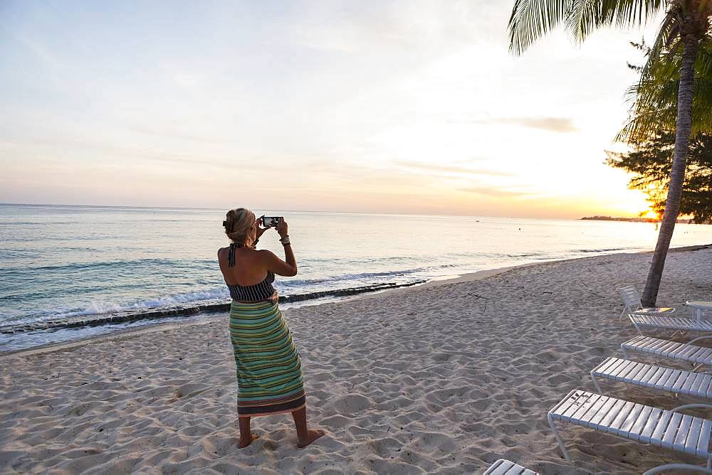 Adult woman taking picture with a smart phone on a beach, Grand Cayman, Cayman Islands