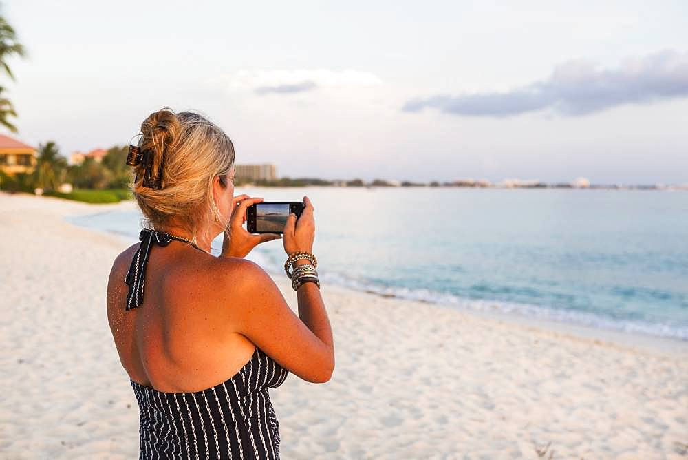 adult woman taking picture with a smart phone, Grand Cayman, Cayman Islands