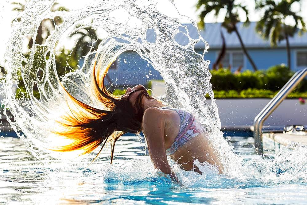 A teenage girl tossing her wet hair back, in pool, Grand Cayman, Cayman Islands
