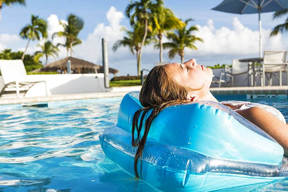 A teenage girl relaxing in a floatie in a pool, Grand Cayman, Cayman Islands
