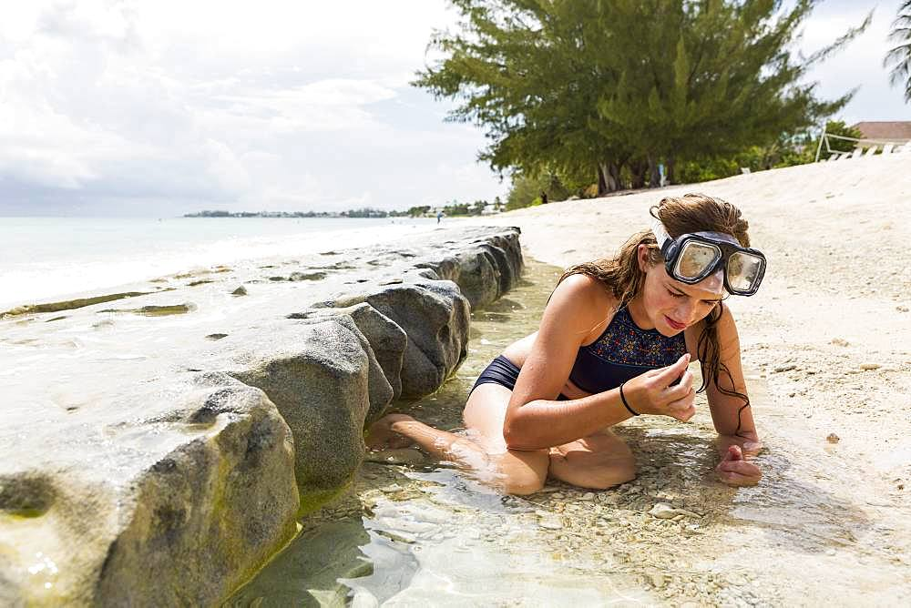 A teenage girl looking at sea glass on the sand, Grand Cayman, Cayman Islands