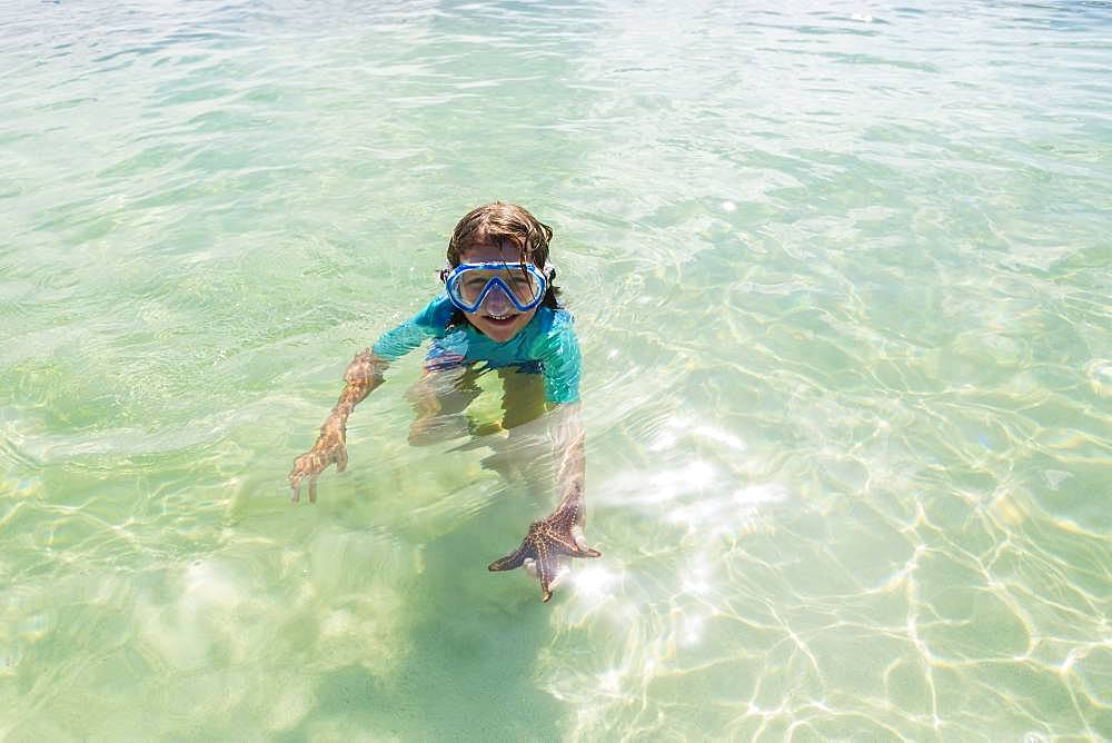 5 year old boy in the water holding a star fish, Grand Cayman, Cayman Islands