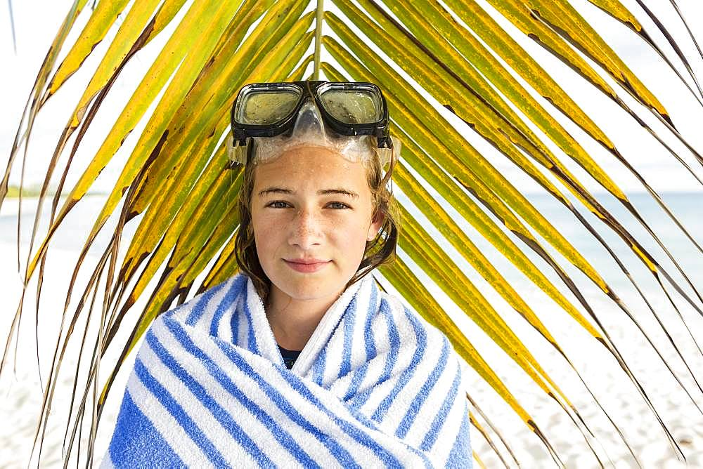 A teenage girl in front of palm fronds, Grand Cayman, Cayman Islands
