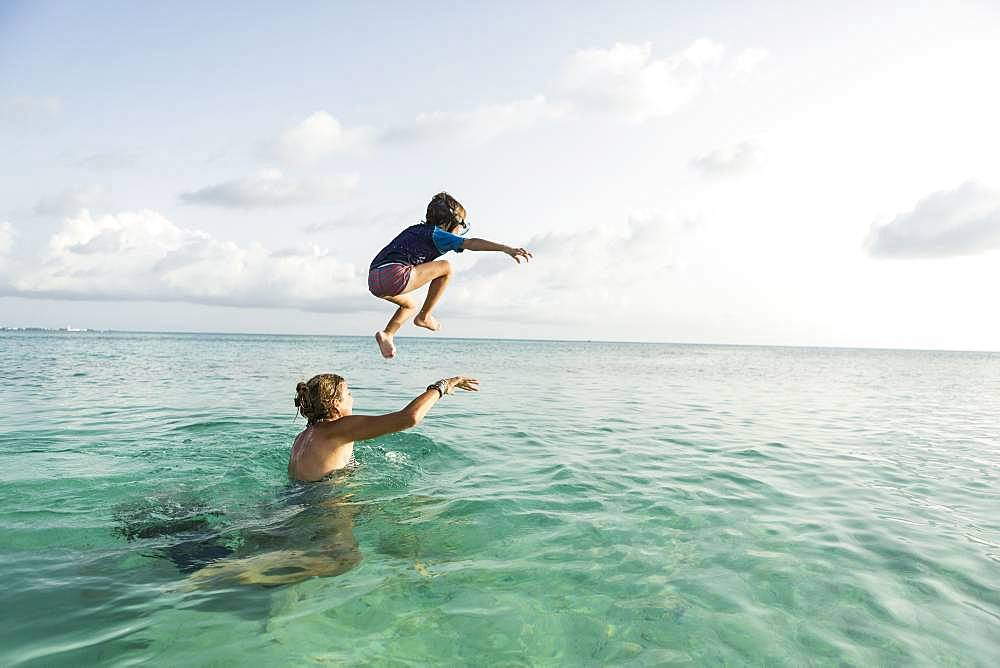 5 year old son on mother's shoulders leaping into the ocean at sunset, Grand Cayman, Cayman Islands
