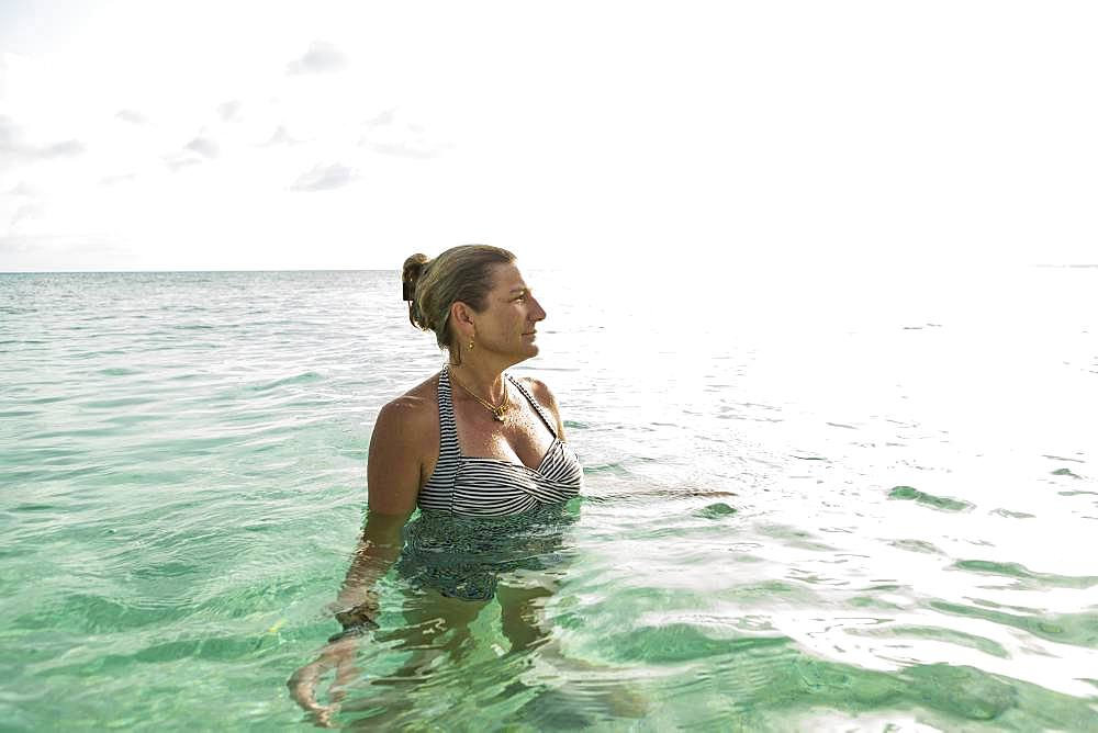 Adult woman standing in ocean water at sunset, Grand Cayman, Cayman Islands