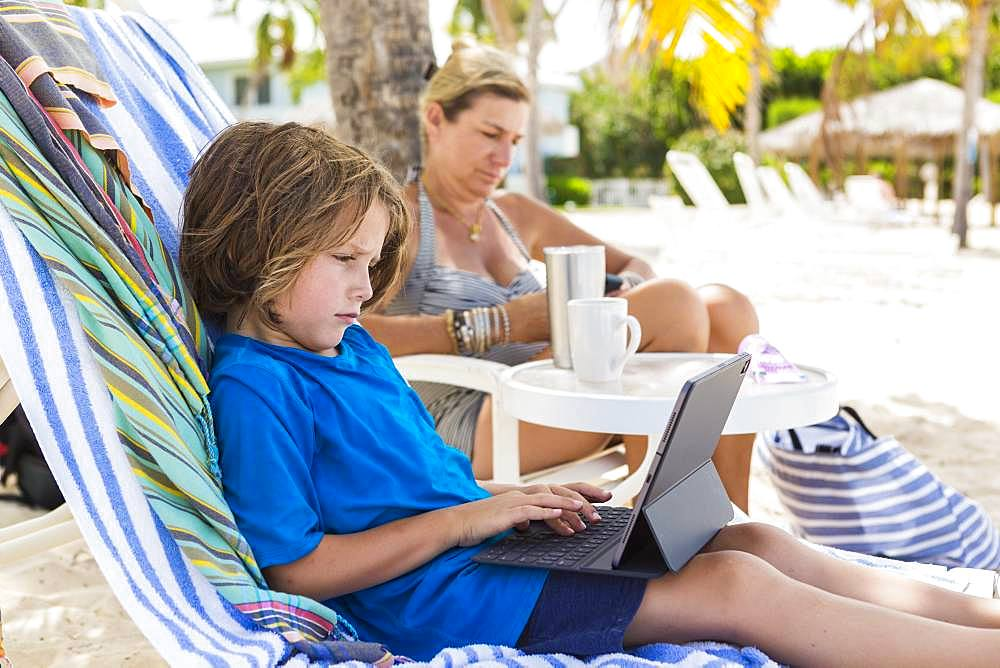5 year old boy using laptop at the beach, Grand Cayman, Cayman Islands