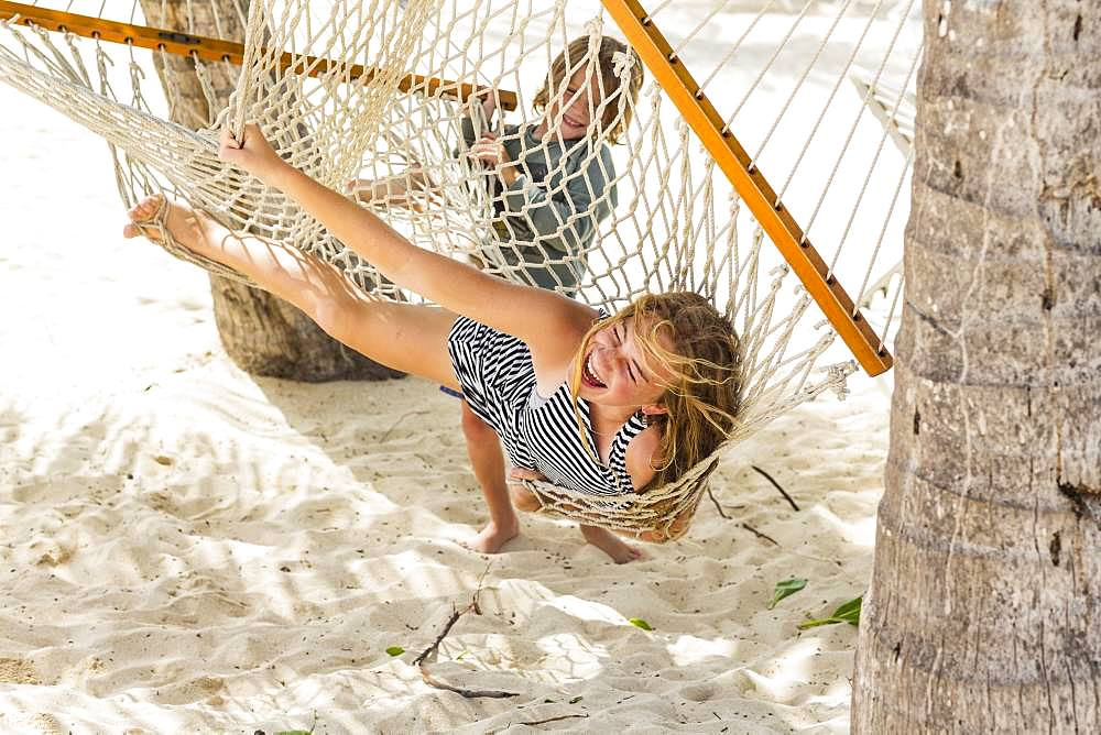 A teenage girl playing in hammock, Grand Cayman, Cayman Islands