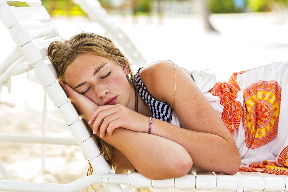 A teenage girl sleeping in beach chair, Grand Cayman, Cayman Islands