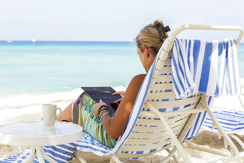 adult woman executive using smart phone on the beach, Grand Cayman, Cayman Islands