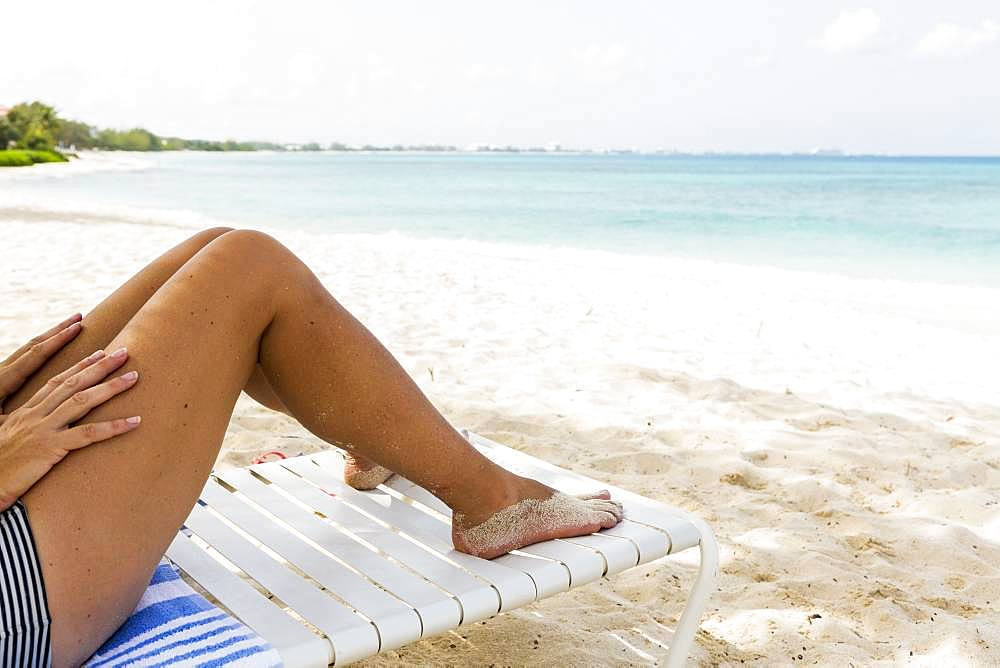 legs of adult woman, overlooking the beach, Grand Cayman, Cayman Islands