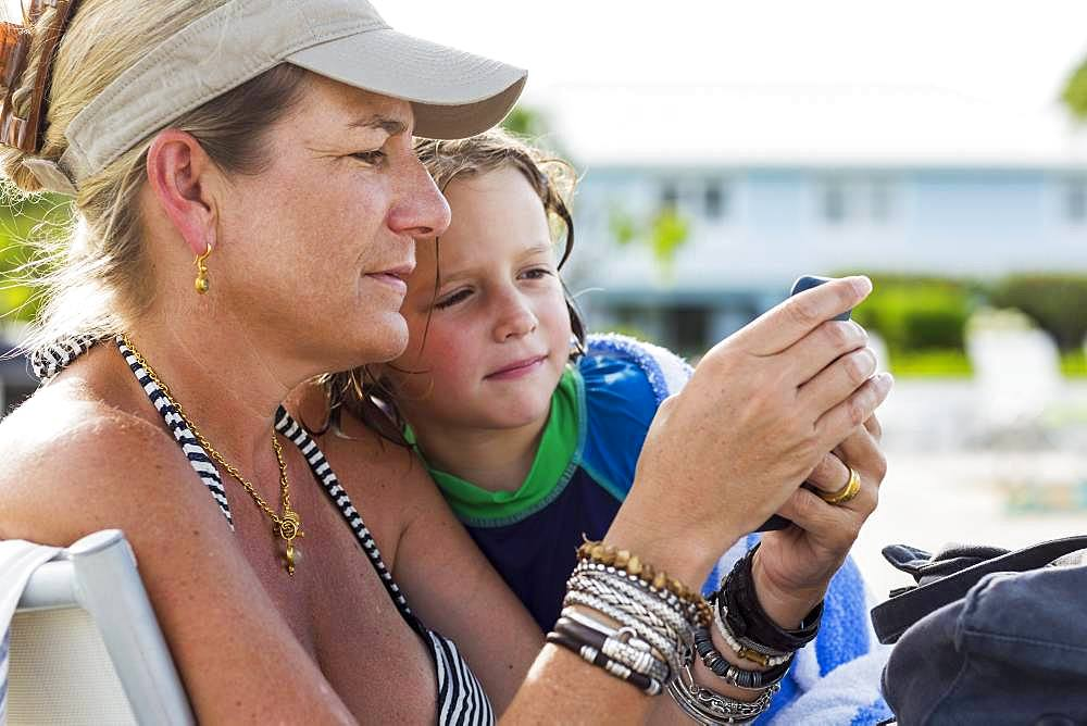mother and 5 year old son looking at smart phone at the beach, Grand Cayman, Cayman Islands