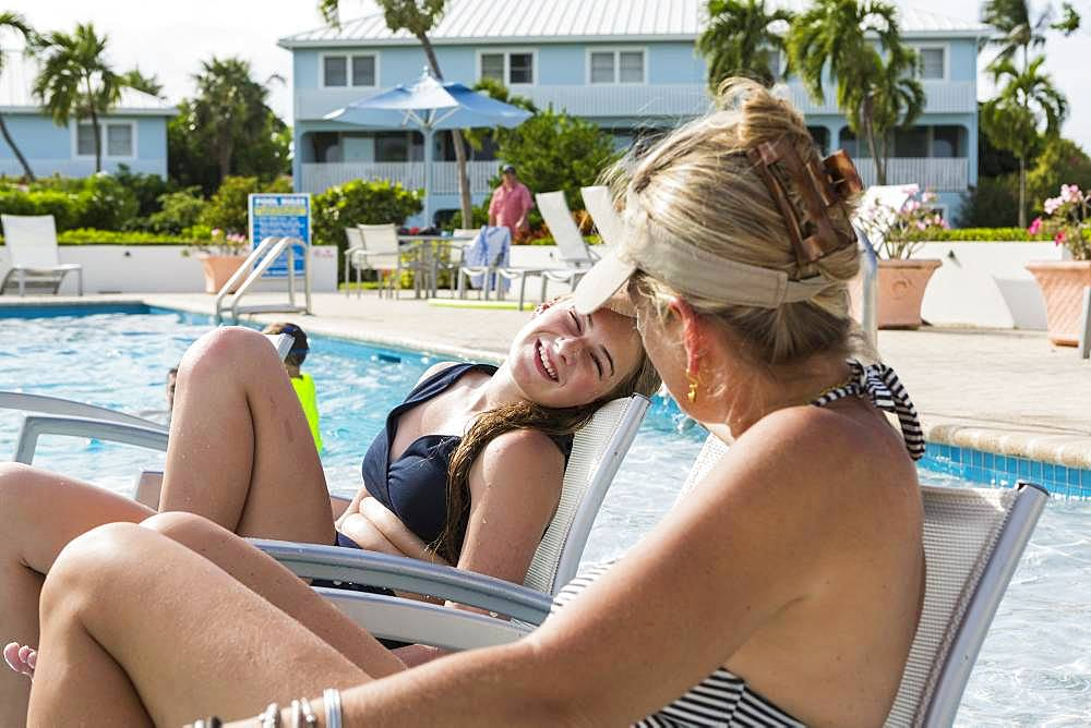 mother and her 13 year old daughter talking by the pool, Grand Cayman, Cayman Islands