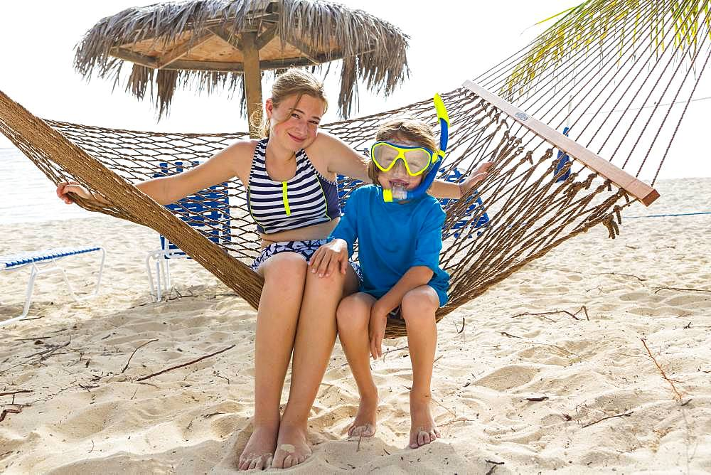 A teenage girl and her brother sitting on a hammock on the beach, Grand Cayman, Cayman Islands