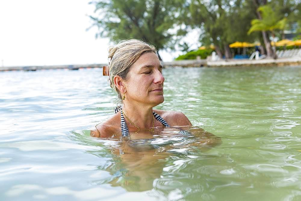 A mature woman relaxing in ocean water, Grand Cayman, Cayman Islands