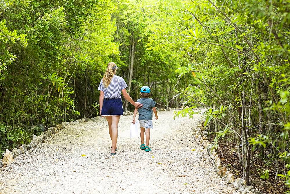 rear view of 13 year old sister and her 5 year old brother walking on nature path, Grand Cayman, Cayman Islands