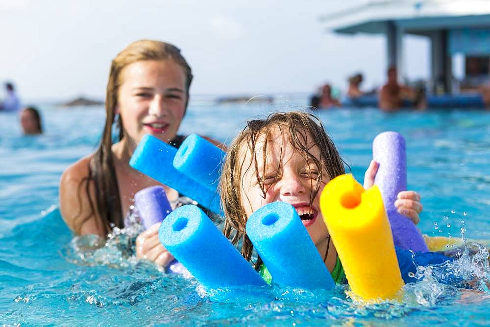 Siblings playing in pool with floaties, Grand Cayman, Cayman Islands